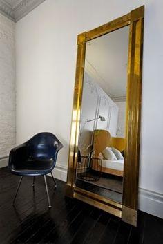 Huge gold mirror + Eames chair.