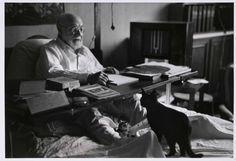 Matisse working in bed, his cats at his feet; Nice, France 1949