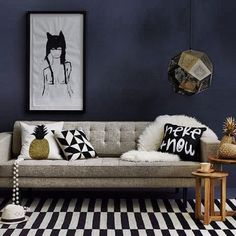 Navy wall, contemporary couch, pillow prints and arrangement, glam throw, side tables, lighting