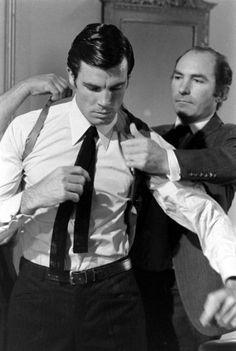 Director Peter R. Hunt helps Robert Campbell get into a shoulder holster.