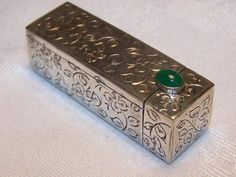 """Solid Silver, compact lipstick case with an automatic mirror. A quality silver piece with a deep green oval onyx cabochon which acts as the clasp, when pulled back the mirror """"pops up"""" -"""