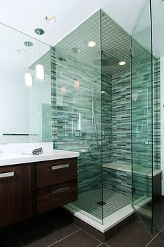Bathroom - Shower with tinted green glass enclosure, bench, rain fall shower head surrounded in aqua tiles.