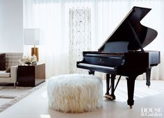 An angora goatskin pouf serves as a bench for a Steinway grand piano in this ethereal Manhattan living room. #houseandgarden