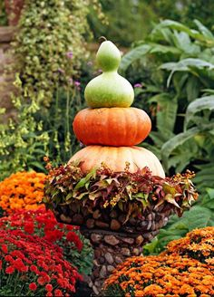 A stack of pumpkins and gourds in an unusual stone birdbath highlights an autumn scene. Mums, fall leaves and berries add even more color.