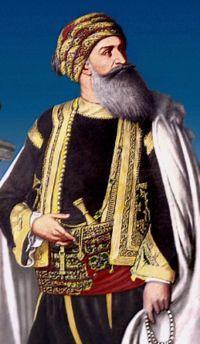 Hussein II Bey, souverain de Tunisie en 1824, en costume ottoman avec gilet et veste brodés, passementeries, pantalon bouffant et large ceinture.