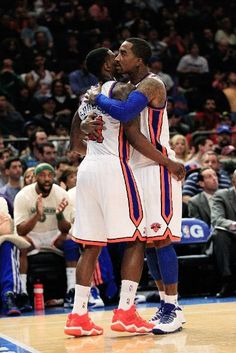 Iman Shumpert #21 of the New York Knicks is embraced by J.R. Smith #8