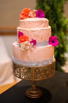 Peach colored wedding cake with Pink and Orange flower accents.
