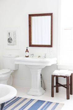 White bathroom with pedestal sink and stripe rug.