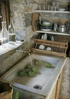 Rustic, farm kitchen sink and stone walls.