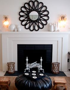 House of Honey  black flower mirror, white fireplace, black leather pouf, and white vases.