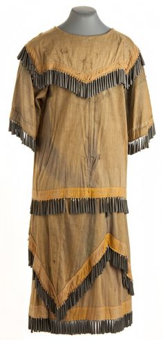 1905 Dakota woman's layered, dyed cotton muslin skirt with tin jingle cones made from tobacco cans. The skirt is part of a Dakota ceremonial jingle dress made by Lucy Pair. This type of dress was traditionally worn for ceremonial healing purposes and, more recently, at pow-wows.