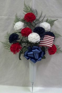 Patriotic cemetery vase of red, white, and blue carnations with an American flag.
