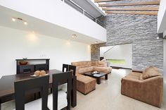 Living room in modern home design.  The room has vaulted sloped ceiling with landing of second floor overlooking the living room space.  Ext...