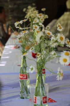 Daisies in coke bottles for an outdoor summer barbeque wedding.