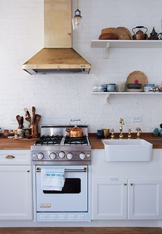 Wonderful little white kitchen with great sink hardware and a perfect little Viking.