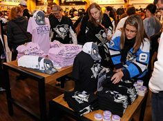 Pittsburgh Penguins fans purchase #HockeyFightsCancer merchandise prior to the game against the Boston Bruins.