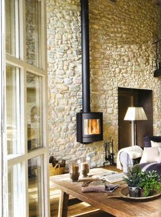 Hermosa manera de resaltar la alta pared de piedra con esta chimenea!