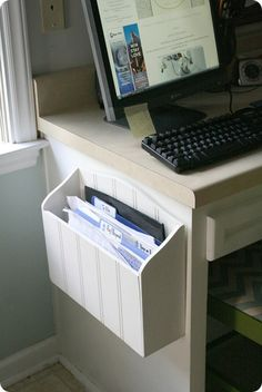 Wooden paper holder screwed to side of a desk. For all the stuff you need to file, but don't want sitting out. Brilliant!