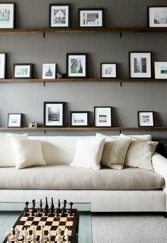 office with dark gray walls, two toned sectional, chess board, and floating picture shelves