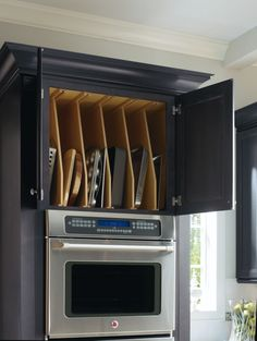 Removable tray dividers easily accomodate oversize items and provide the perfect storage space when not in use. By Thomasville Cabinetry.