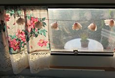 Flower strung lighting & floral curtains. Glamping.