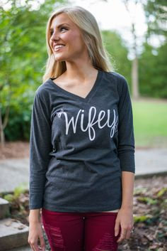 """Let the world know that you are a Proud Wifey with this super soft grey tee! The fit is beyond flattering and how gorgeous is that font? What a precious bridal gift this would make! It's perfect for easy honeymoon wear or to simply let those other jokers know you're eternally taken! ;) <br /> <br />Bra-friendly! Material has fair amount of stretch. <br />Lauren is wearing the small. <br /> <br />Length from shoulder to hem: S- 25""""; M- 26""""; L- 27""""."""