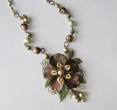 """September challenge parure (necklace part): """"Yesterday's Dream."""" The necklace has a  handmade polymer clay flower and leaves on a B'Sue filigree, and Spectra beads and brass flower/leaves from B'Sue Boutiques; glass pearls finish it off.  The matching bracelet and earrings use Spectra beads from B'Sue Boutiques.  By Novegatti Designs   www.facebook.com/NovegattiDesigns"""