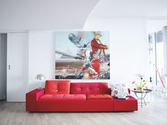 Red sofa & bold artwork via Planete Deco