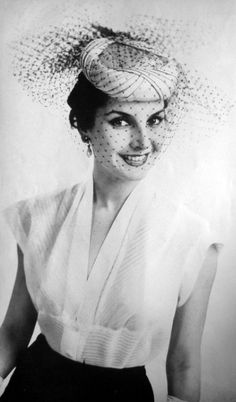 Model wearing a hat with veil for La Femme Chic, 1956.