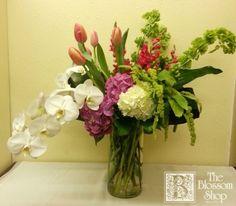 Luxurious, modern arrangement in a tall cylinder vase.