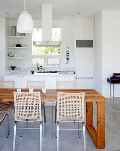 The white color scheme lets her furnishings and belongings take center stage in the space. The kitchen cabinets are from Ikea.