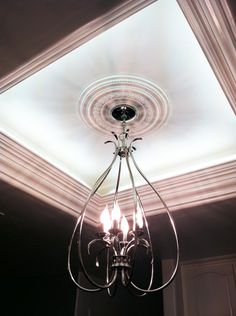 Move flourescent bulbs to perimeter, mask with crown moulding, hang chandalier from center wiring. Perfect for that ugly light box in the kitchen!