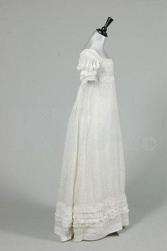A sprigged muslin day dress, circa 1825, embroidered overall with minute leaves and flowerheads, puffed cutwork sleeves edged in ruffles of muslin, similar broad ruched band to hem.