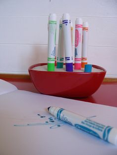 This marker holder holds 8 Crayola nontoxic washable markers upside down in a red melamine bowl filled with plaster of paris. It is great for very young children (and older ones!) making it easy to put the markers back in their caps. The marker holder is an effective way to store markers yet keep them within reach for regular use.