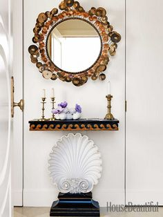 A Raindrops mirror by C. Jere hangs over a vintage Edward Wormley shell console table.