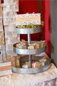 Cute little wedding favor boxes in tiered stand. Captured By: Stephanie N. Baker ---> http://www.weddingchicks.com/2014/06/06/funky-finds-turned-into-surprising-centerpieces/