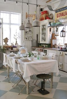 "Eclectic Farmhouse style that is welcoming and cozy.  Wooden counter tops...a simple floor...vintage glass cabinets along with vintage ""industrial"" style lighting just makes you want to sit down and break bread with family and friends."