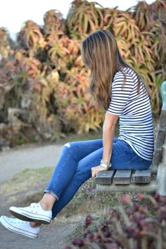 Striped mid-sleeve shirt, jeans, and white Converse.