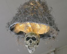 "This is still one of my all-time favourite ""quick and dirty"" projects. I saw one like this online, but it was way too much money. So, a little spray paint, some jute, a super cheap lampshade, a little Spanish Moss, an old skull; and voilà! Super creepy front entry lighting."