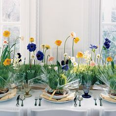 """A narrow garden path cuts across the table, sprouting an airy array of brightly hued spring blooms—purple anemones, yellow poppies and ranunculus, white narcissus and hellebores, and blue hyacinths. Use whatever is in season and """"plant"""" with a light hand so conversations spark across the garden. Florist's flats of wheatgrass were cut to cover the length of the table, then planted with flowers, each in a water tube. table decorations, floral centerpieces, idea, table flowers, flower centerpieces, garden parties, table centerpieces, spring blooms, wedding centerpieces"""