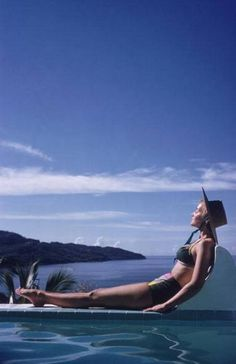 Photographer Inge Morath sunbathes in Acapulco, 1960. Photo by Slim Aarons.