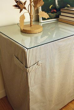 cover a large dog crate w/ a skirt and a finished piece of glass to make a duel-purposed table.