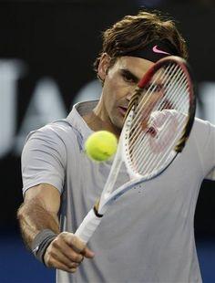 Switzerland's Roger Federer makes backhand return to Australia's Bernard Tomic during their third round match at the Australian Open tennis championship in Melbourne, Australia, Saturday, Jan. 19, 2013. (AP Photo/Andy Wong)