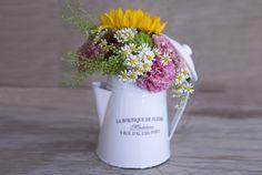 Cafetera de metal esmaltado con arreglo de flores de temporada
