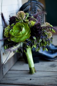 Rustic country bridal bouquet of green succulents, purple artichokes, green celosias, purple and green agapanthus and brown scabiosa pods. This summer wedding bouquet is ideal for the bride who wants something unique and different. Outdoor photo shoo