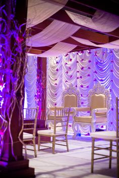 Mandap with white silk backdrop and strings of purple orchids via IndianWeddingSite.com