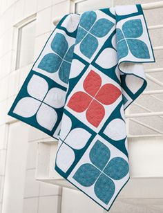 This quilt pattern featured in Quilty September/October 2013 is a throw size quilt pattern that features appliqué petals in blue and white with one burst of red. Further proof that quilts are cool. Quilt by Jenifer Dick. Quilted by Kris Barlow.