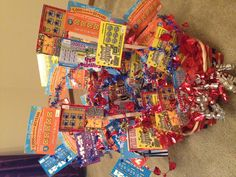 This is a Lotto ticket birthday bouquet!  The birthday boy is 70- so I got 70 Lotto tickets and went to the Dollar store.  Just choose a cute basket and find a foam florist ring!  Tape the Lotto tickets to Popsicle sticks at varied heights and stagger them in the foam.  We added ribbons and colored paper to finish it up!  Viola!  This would work great with gift cards too!!