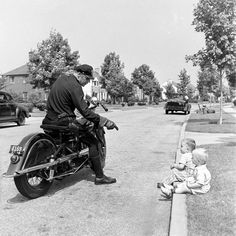 A policeman chatting with toddler boys. Garden City, NY, 1942, by Alfred Eisenstaedt
