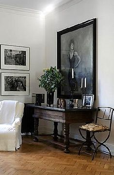 dark console table and white slipcovers and artwork over the table